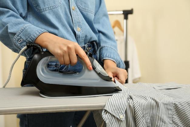 アイロンでシャツにアイロンをかけるジーンズの女性