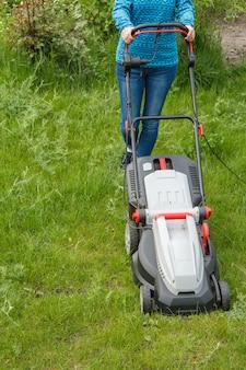 청바지를 입은 여성이 화창한 여름날 정원에서 잔디 깎는 기계로 작업하고 있습니다. 잔디 깎는 기계. 정원사 관리 작업 도구를 깎습니다.