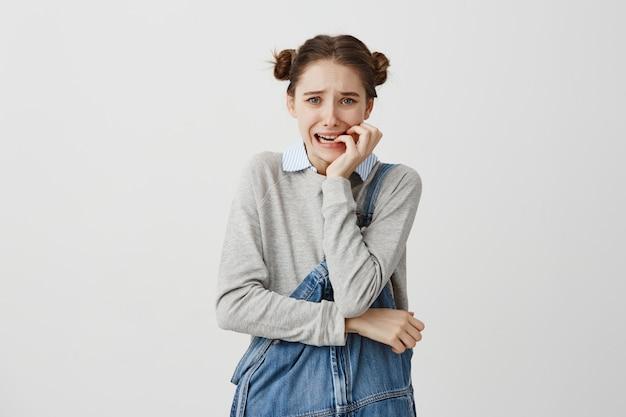ストレスを見て恐怖を感じて爪を噛んでジーンズジャンプスーツの女性。彼女の失敗を心配するトラブルを経験している女性ビジネス初心者。人間の感情