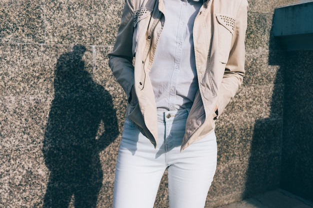 청바지, 셔츠와 대리석 벽의 배경에 베이지 색 재킷을 입은 여자