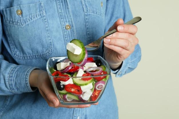 Женщина в джинсовой рубашке ест греческий салат