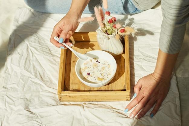 청바지를 입은 여성이 침대에 앉아 아침 햇살 동안 건강한 그래놀라 그릇을 먹고, 침대에서 아침을 먹습니다.