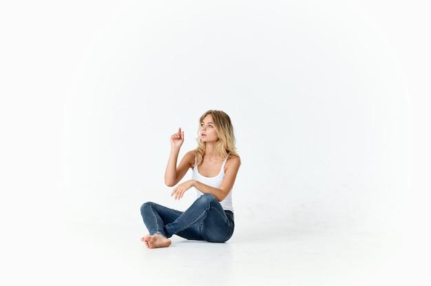 床に座っているジーンズの女性楽しい感情スタジオ孤立した背景