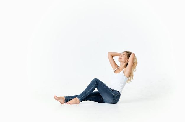 패션 라이프 스타일을 포즈 바닥에 앉아 청바지에 여자