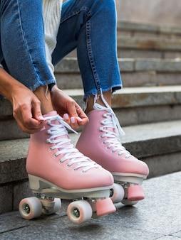 Женщина в джинсах завязывает шнурки на роликах