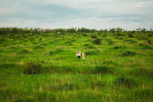 ハンカチの女性と牧草地を歩いている男性