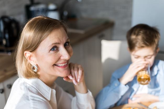 台所の女性は子供の飲み物ジュースを背景にカメラを見て