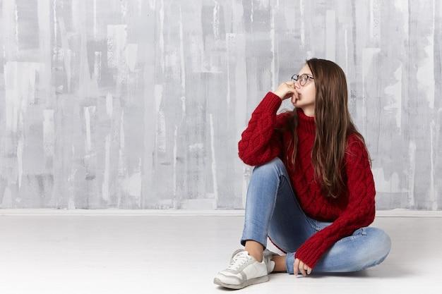 ニットの居心地の良いセーター、眼鏡、ジーンズ、スニーカーの女性が床に座って、物思いにふける表情で目をそらし、10代の問題について考えています
