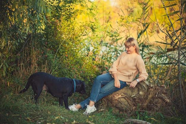 짧은 머리를 한 니트 스웨터를 입은 여성이 쓰러진 나무에 앉아 있고 검은 로트와일러 개가 숲에서 뛰어다닌다