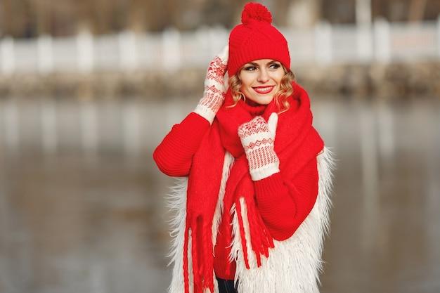 Женщина в вязаной зимней шапке и шарфе смотрит в камеру с улыбкой