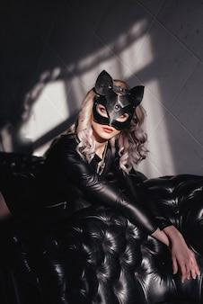 Женщина в латексном и кожаном костюме черного кота