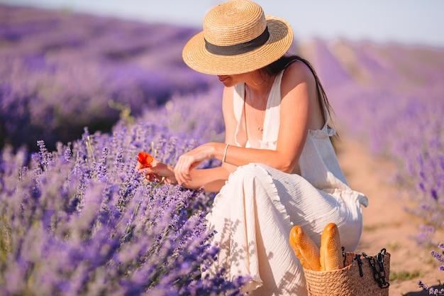 白いドレスと帽子で夕暮れ時のラベンダーの花のフィールドの女性