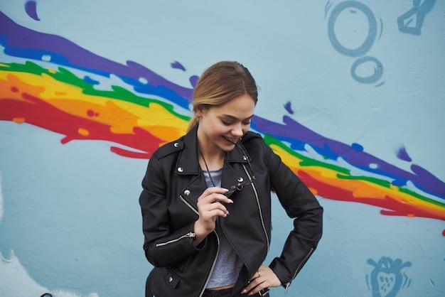 通りの色とりどりの壁の近くの革のジャケットの女性