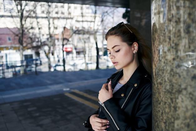 街の通りの革のジャケットと背景のエディションのサングラスの女性
