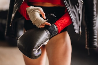 Woman in leather jacket puts on boxing gloves