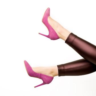 白い背景の上の革のズボンとピンクのハイヒールの靴の女性。 -画像