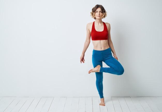 レギンスを着た女性が脚を曲げてヨガフィットネス瞑想