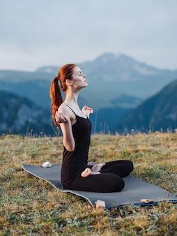 레깅스를 입은 여성은 산의 자연에 깔개에 앉아 명상을합니다.
