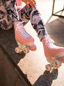 Женщина в леггинсах позирует с роликовыми коньками