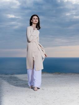 海と青い空を背景に明るい服を着た女性 Premium写真