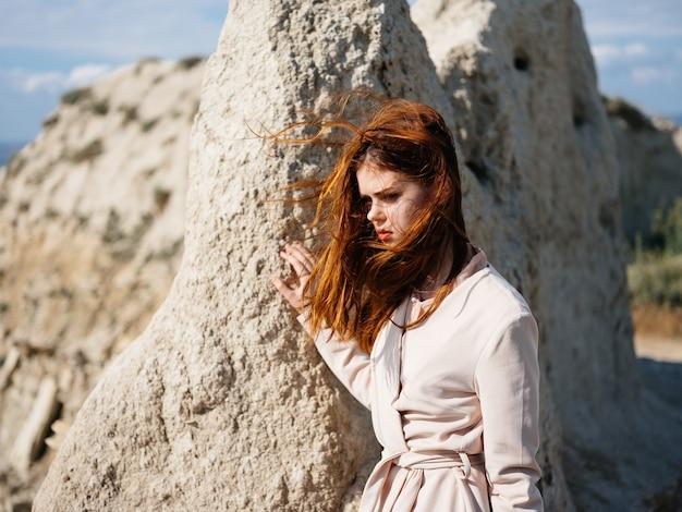 野外で大きな石の近くの薄着の女性