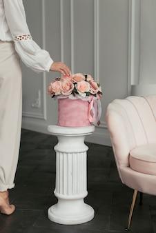 薄着の女性が手でシックなピンクの花の花束に触れます