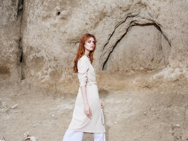 山の自然の高い石の近くの薄着の観光客の女性
