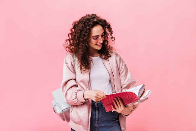 Женщина в легкой одежде читает заметки в блокноте на розовом фоне