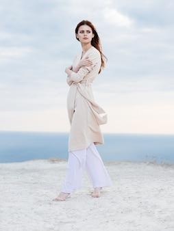 軽いズボンとセーターを着た女性が背景の自然の海の山を旅します