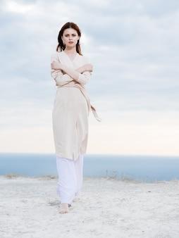 가벼운 바지와 스웨터를 입은 여성이 자연의 바다에 산을 여행합니다.