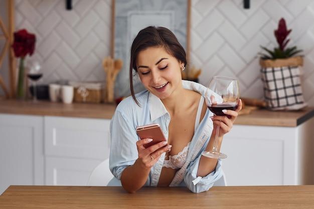 가벼운 옷을 입은 여성이 와인을 마시며 부엌에 있습니다.