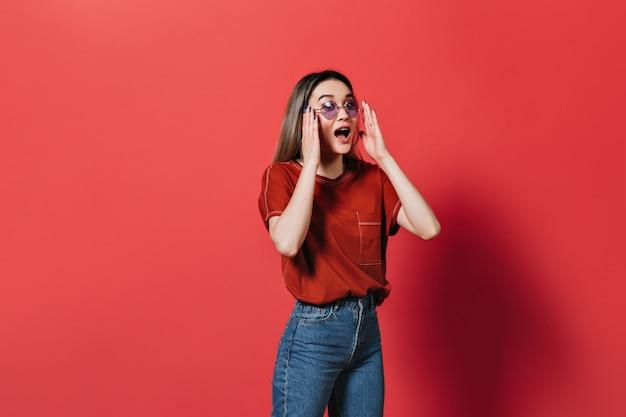 薄紫色のメガネと赤いtシャツの女性が孤立した壁に感情的にポーズをとる