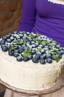 Женщина в сиреневой рубашке держит праздничный домашний белый торт на день рождения с органической черникой и мятой