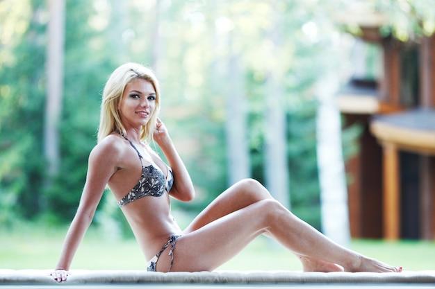 Женщина в нижнем белье, расслабляясь на диване на открытом воздухе