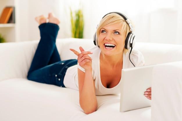 音楽を聴いているリビングルームの女性