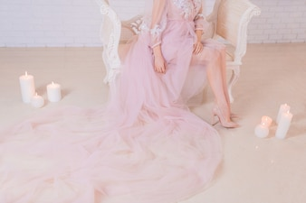 Woman in long pink dress sits on a chair surrounded with shiny candles