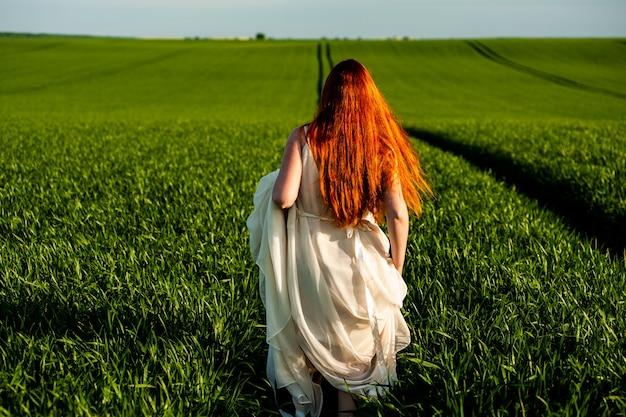 Женщина в длинном белом платье на зеленом поле