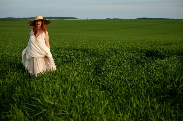 緑の野原で屋外の長い白いドレスを着た女性