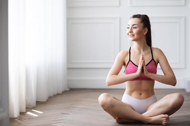 Женщина в позе лотоса. йога дома.