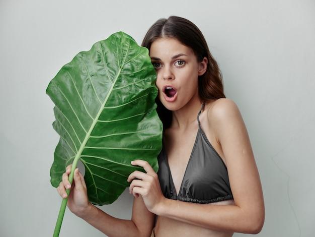 彼女の手に緑の葉を持つ灰色の水着で恋をしている女性自然エキゾチック