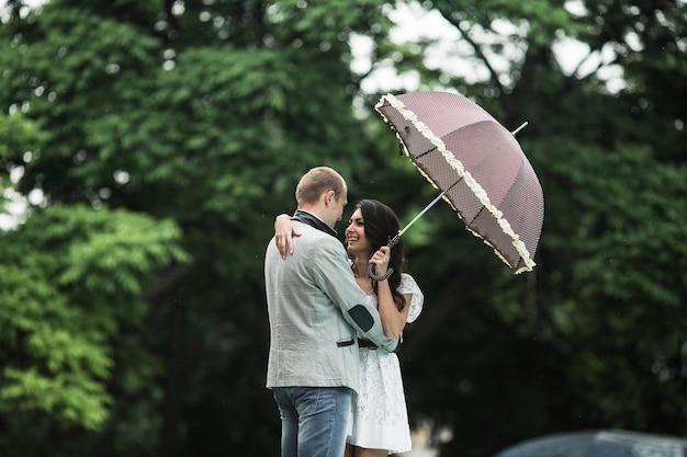 Женщина в любви с зонтиком, глядя на своего друга