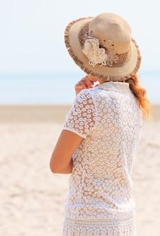 Женщина в роскошной шляпе, глядя на море