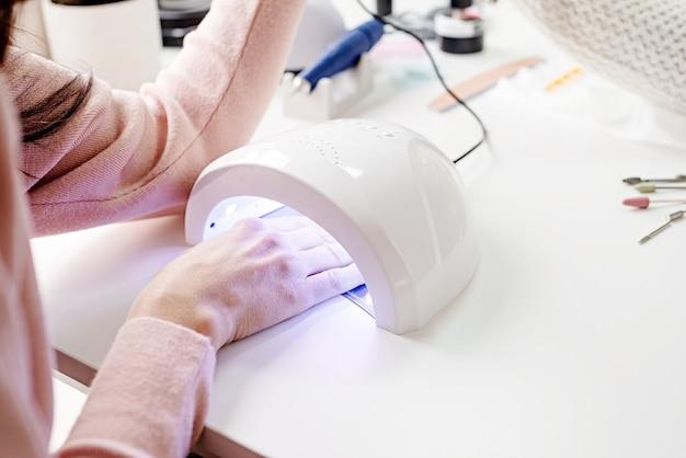 Женщина в маникюрном салоне сушит ногти в уф-лампе