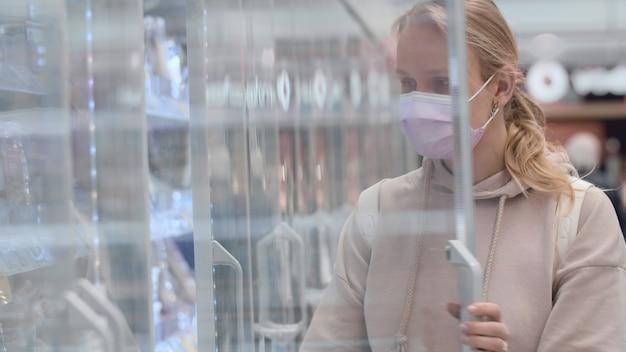 Женщина в маске покупает йогурт в супермаркете