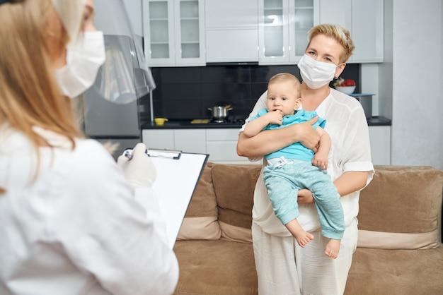 Женщина в маске, несущая мальчика, пока доктор пишет в буфер обмена