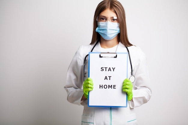 Женщина в маске держит бланк с надписью остаться дома, призывая остановить распространение covid-19.