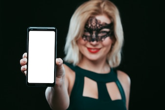 Woman in mask holding smartphone
