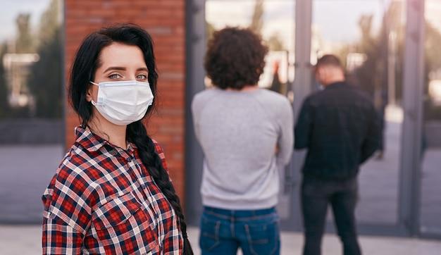 큐에서 사회적 거리를 유지하는 마스크에 여자