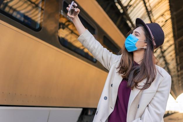 Женщина в маске, делающая селфи на вокзале