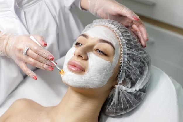 의료 모자에있는 여자 미용사의 얼굴에 마스크를 만드는